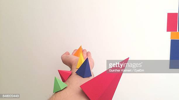 Multi Colored Paper Pyramids On Man Hand