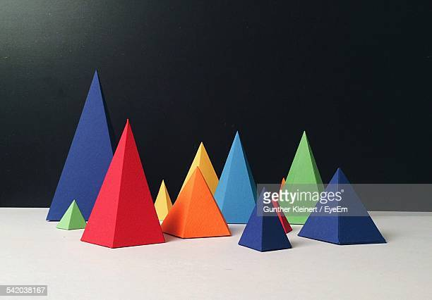 Multi Colored Paper Pyramids On Table Against Black Wall