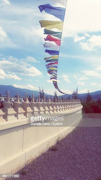 multi colored praying flags hanging over temple against sky - hertz stock pictures, royalty-free photos & images