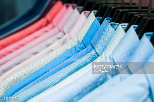 multi colored shirts hanging on the closet - men fashion stock pictures, royalty-free photos & images