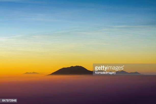 Multi colored sunrise silhouetting volcano