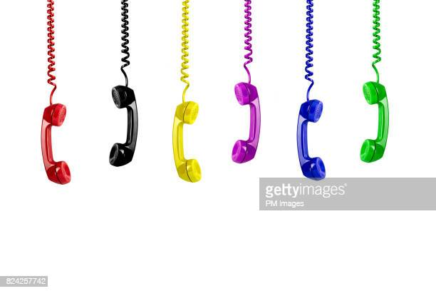 Multi colored telephone receivers hanging down