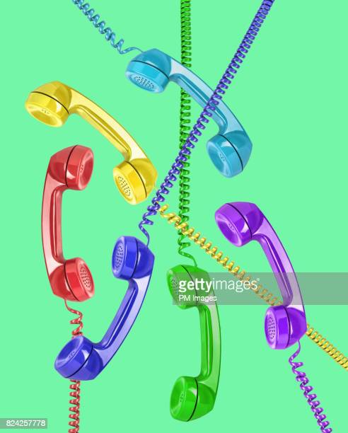 6 multi colored telephone receivers on green