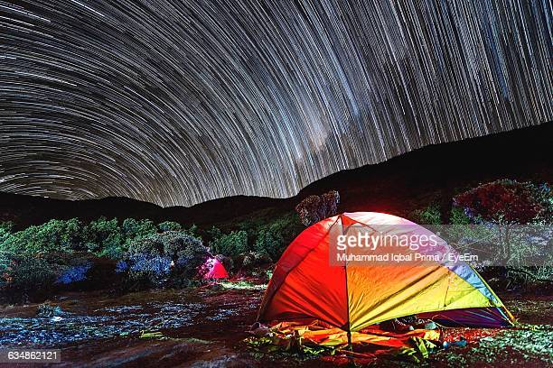 Multi Colored Tent Against Star Trails At Night