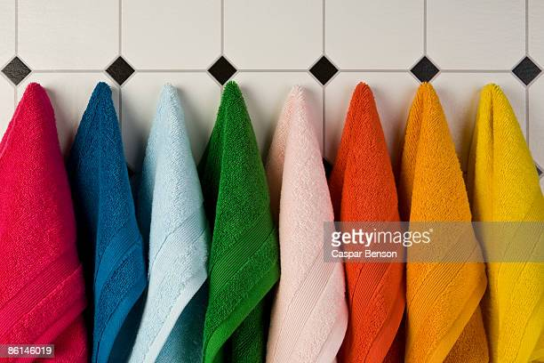Multi colored towels hanging in a row on the wall