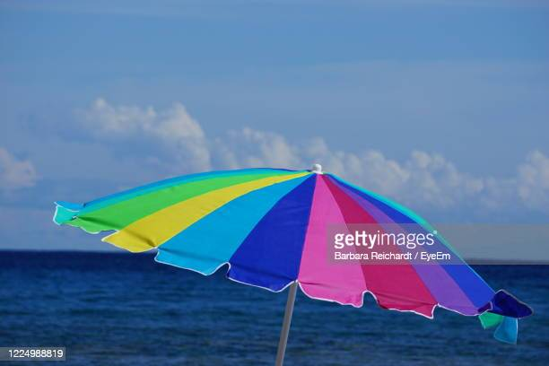 multi colored umbrella on beach against sky - hawaii flag stock pictures, royalty-free photos & images