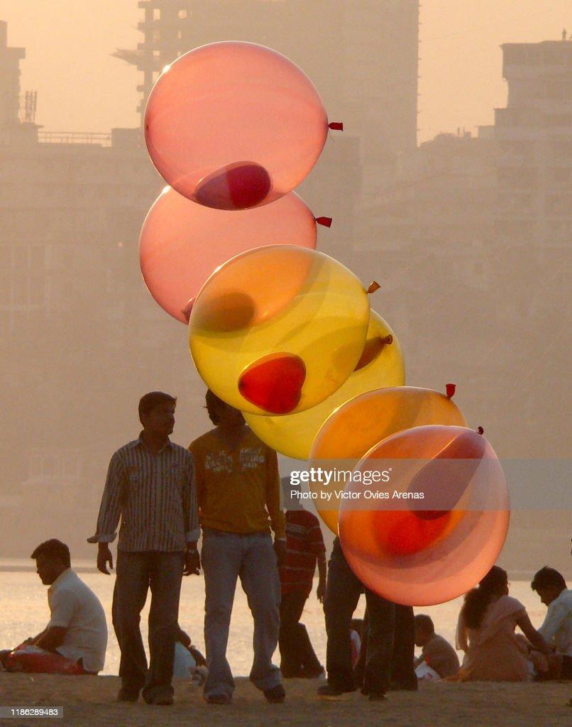 Multi coloured balloons and people on Chowpatty beach at sunset in Mumbai, Maharashtra, India : Foto de stock