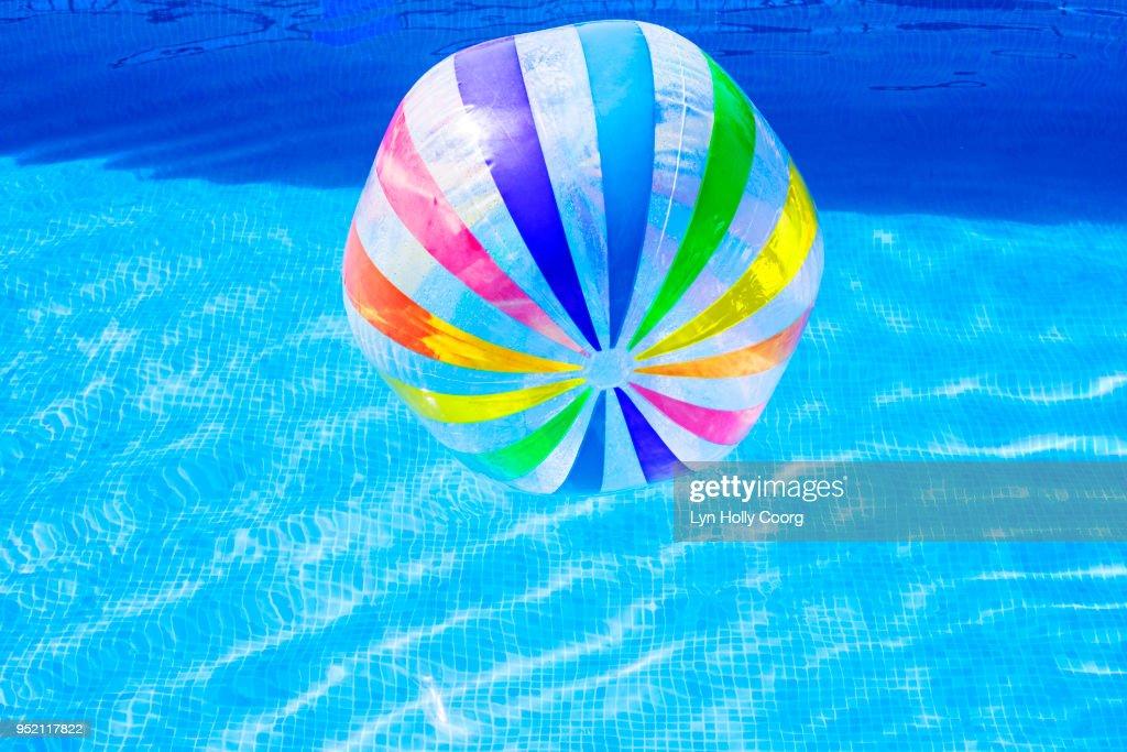 Multi coloured beach ball in swimming pool : Stock Photo