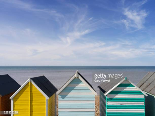 multi coloured beach huts and sky - beach stock pictures, royalty-free photos & images