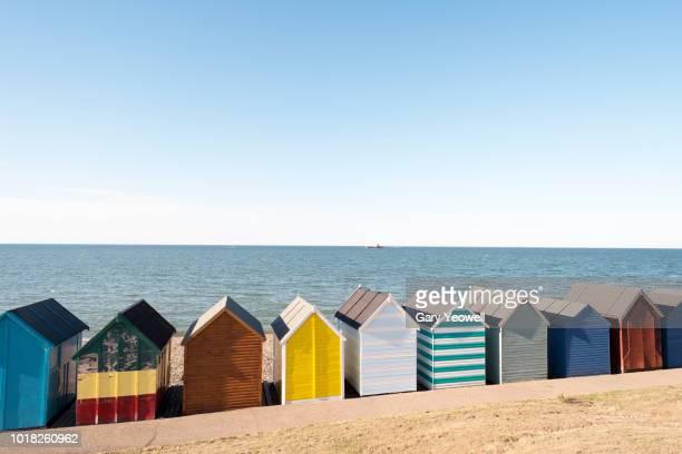 multi coloured beach huts by the sea - südostengland stock-fotos und bilder