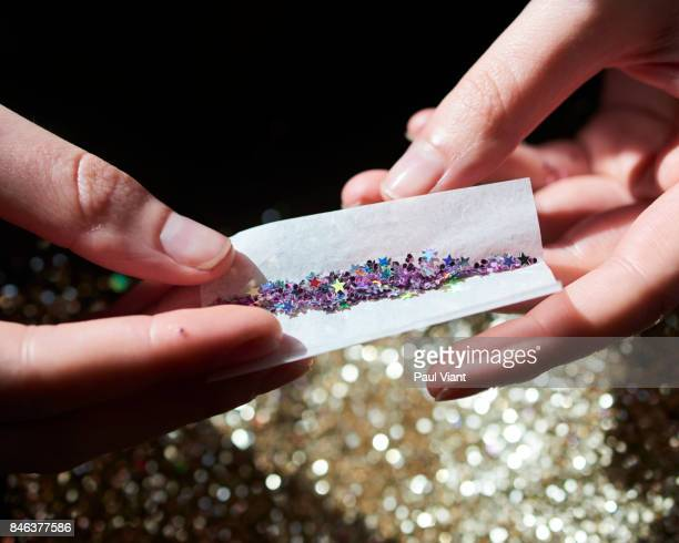 multi coloured glitter being rolled in cigarette paper