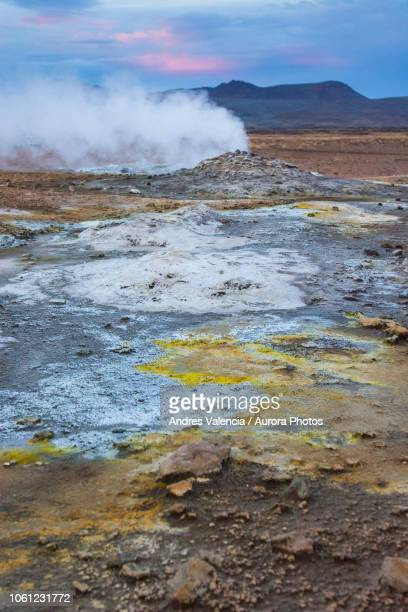 Multi coloured soil and active steam spring with Namafjall in the background, at Hveraröndor Hverir Geothermal Area, at Namaskard Pass in Iceland.