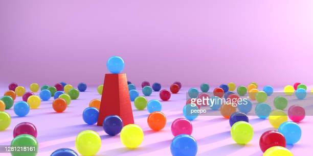 multi coloured spheres surrounding a single sphere on a plinth - ball stock pictures, royalty-free photos & images