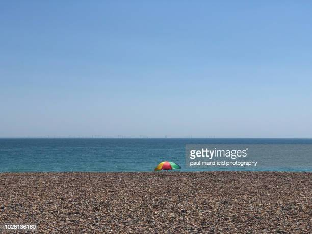 multi coloured sun umbrella on beach - pebble stock photos and pictures