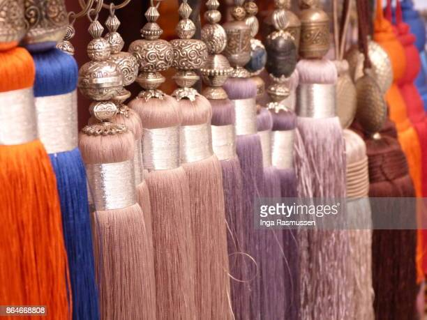 multi coloured tassels on display in the souk, marrakesh, morocco - fringing stock photos and pictures