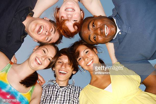 multi cultural circle of friends with their heads together - teenagers only stock pictures, royalty-free photos & images