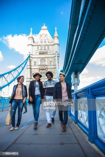 multi cultural group of friends hanging out in central london, on the tower bridge. - central london stock pictures, royalty-free photos & images