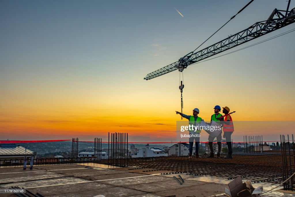 Multi ethic workers talking at construction site reviewing plans : Stock Photo