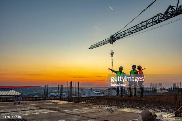 multi ethic workers talking at construction site reviewing plans - roof stock pictures, royalty-free photos & images