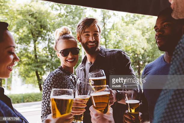 Multi ethinc friends toasting with beer outdoors