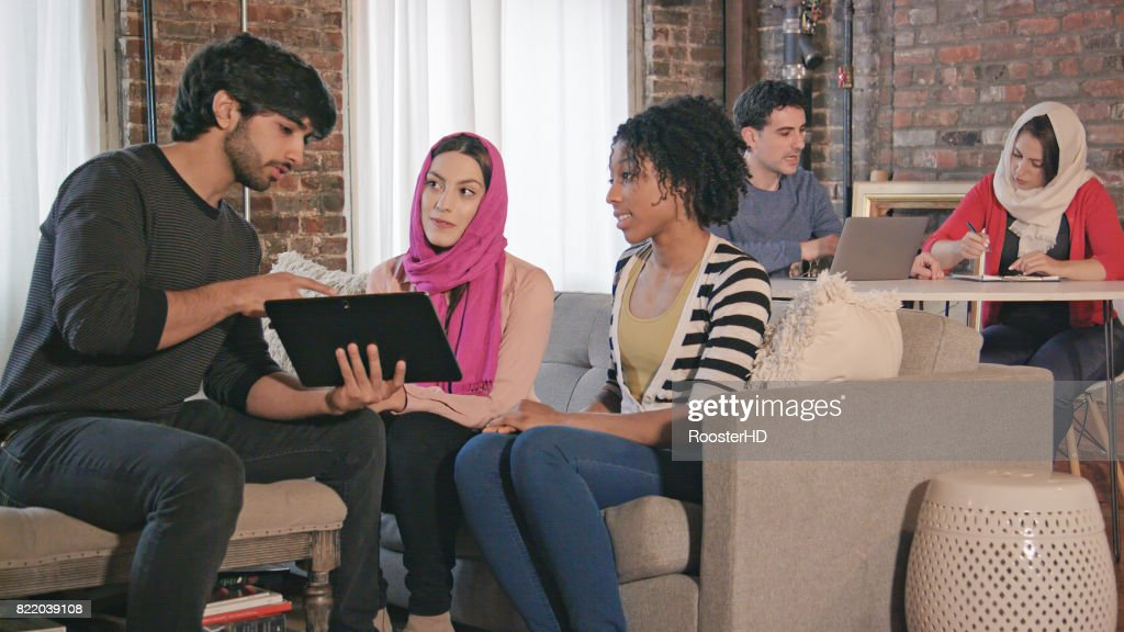 Multi Ethnic Adults Interact with Digital Tablet : Stock Photo