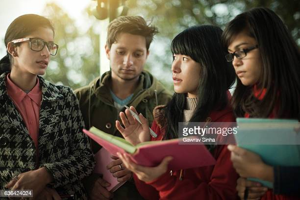 Multi ethnic Asian university students teaching and learning together.