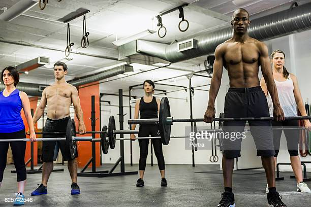 Multi ethnic athletes lifting barbells in gym