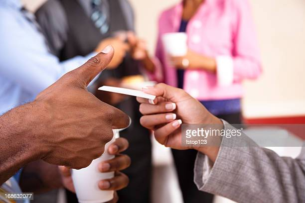 Multi ethnic Business card exchange social with refreshments