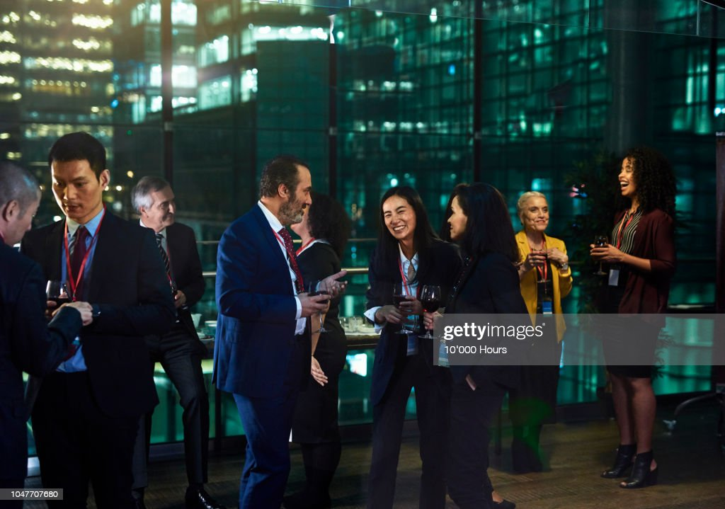 Multi ethnic business colleagues socialising at office party : Stock Photo