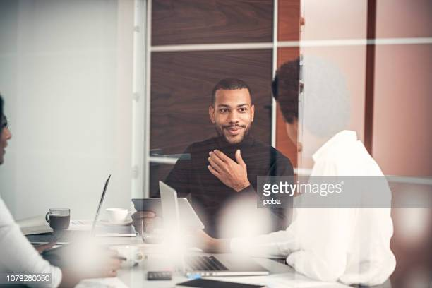 multi ethnic business coworkers discussing during meeting  at office - business finance and industry stock pictures, royalty-free photos & images