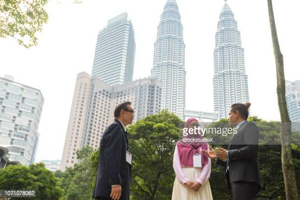 multi ethnic business team having a outdoor meeting - kuala lumpur stock pictures, royalty-free photos & images