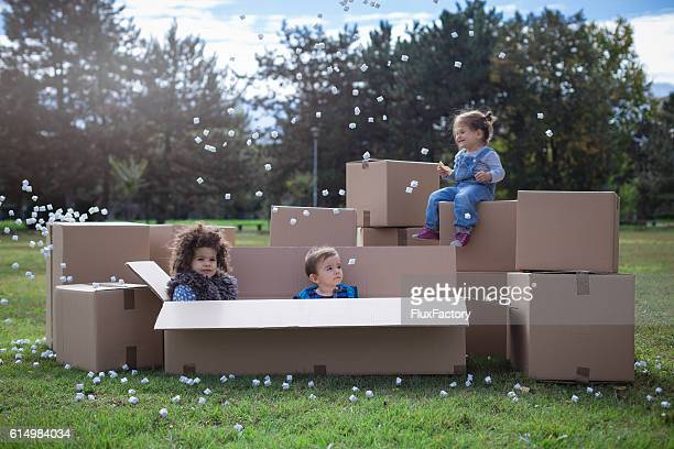 multi ethnic children playing with cardboard boxes - free images for educational use stock pictures, royalty-free photos & images
