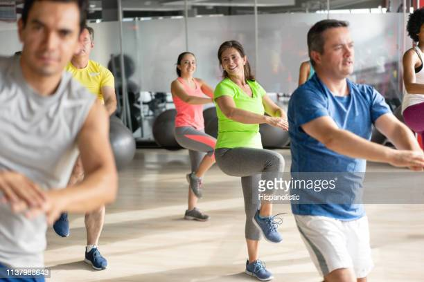 multi ethnic class at the gym warming up with different exercises - hispanolistic stock photos and pictures
