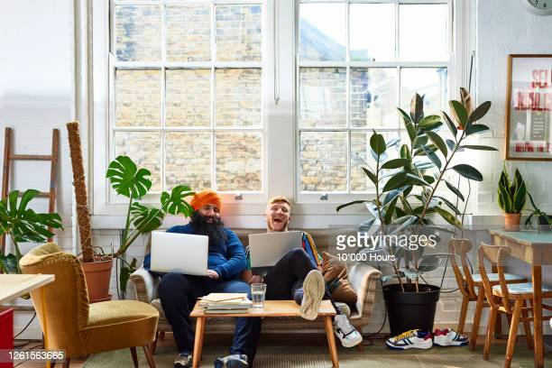 multi ethnic colleagues laughing on sofa at work - headwear stock pictures, royalty-free photos & images