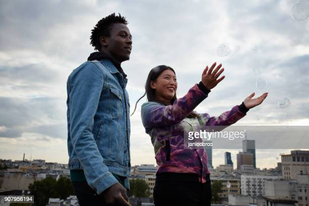 Multi ethnic couple hugging on the rooftop. Enjoying soap bubbles