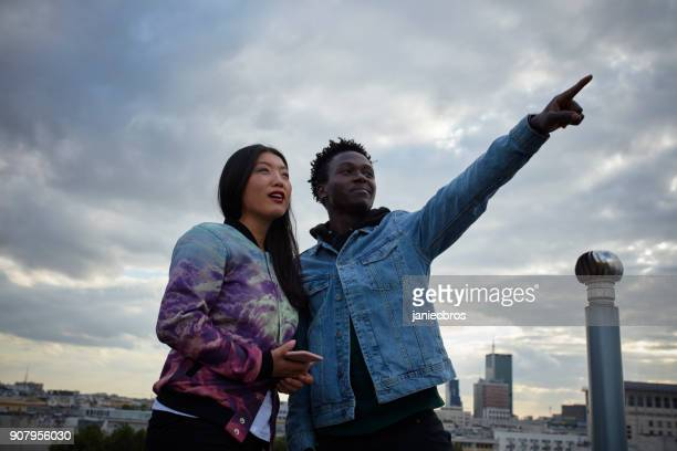 Multi ethnic couple hugging on the rooftop. Enjoying the view