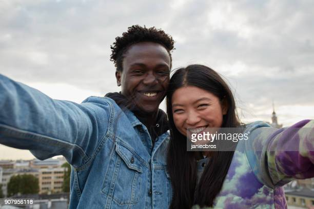 Multi ethnic couple hugging on the rooftop. Making selfie