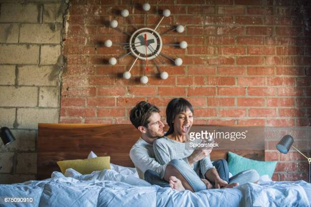 multi ethnic couple in bed being proposed to - black women engagement rings stock pictures, royalty-free photos & images
