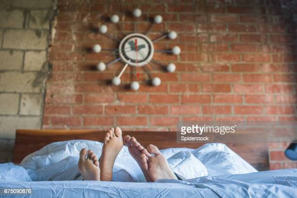 multi ethnic couple in bed - black men feet stock photos and pictures