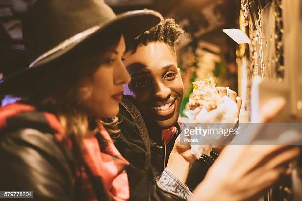 Multi ethnic couple in burger pub, close up of faces