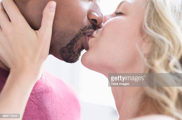 multi ethnic couple kissing - black people kissing stock pictures, royalty-free photos & images