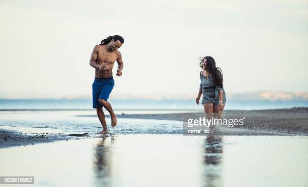 Multi ethnic couple running in water and having fun.