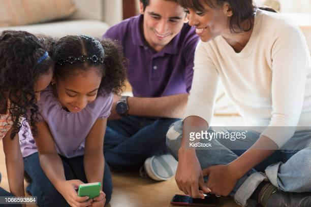 Multi ethnic family having fun looking at pictures using smart phone
