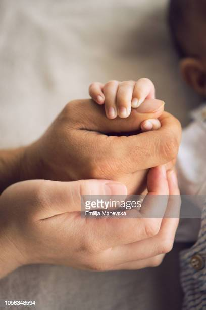 multi ethnic family holding hands together - black people praying stock pictures, royalty-free photos & images