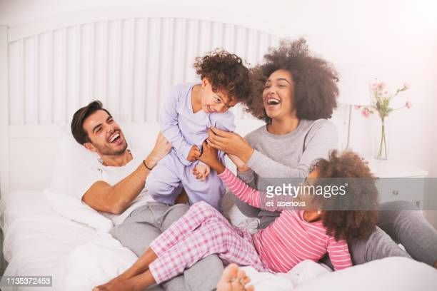 multi ethnic family playing together on the bed - white wife black baby stock photos and pictures