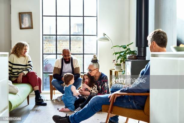 multi ethnic family relaxing on weekend in living modern room - multi ethnic group stock pictures, royalty-free photos & images