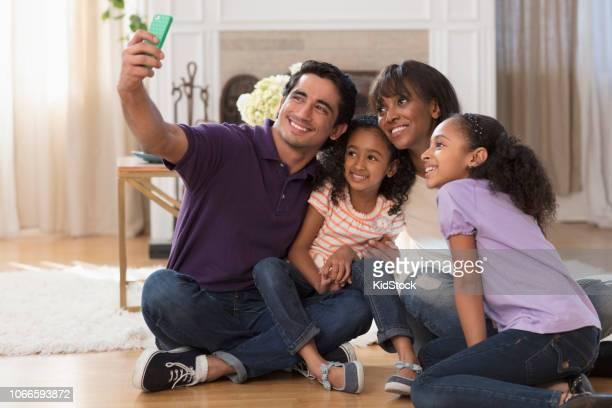 Multi ethnic family taking selfies sitting on floor