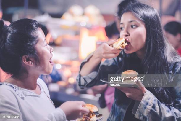 Multi ethnic female friends enjoying street food.