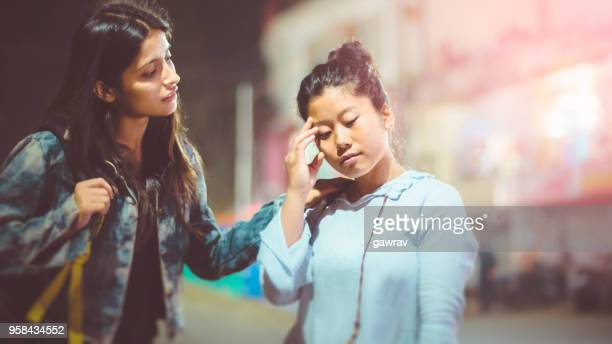 multi ethnic female friends together on street at evening. - medical condition stock pictures, royalty-free photos & images