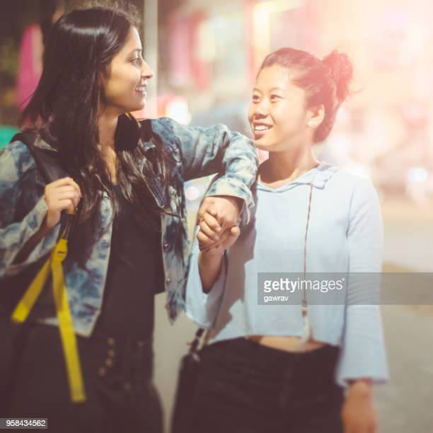 multi ethnic female friends together on street at evening.